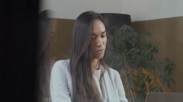 jovem mestiça sentada à mesa, fazendo videochamada
