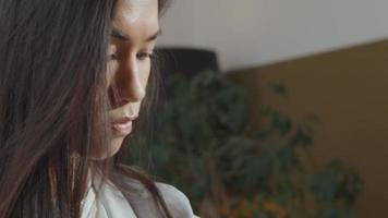 close-up de uma jovem mulher de raça mista, tocando em seu smartwatch