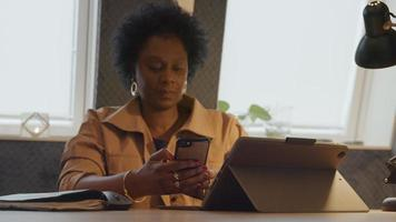 Mature black woman sits at table, holding mobile phone in hands, touching screen