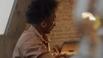 rijpe zwarte vrouw zit aan tafel en heeft een videogesprek video