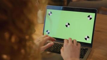 närbild av grön skärm på bärbar dator, fingrar av ung vit kvinna skriver på tangentbordet video