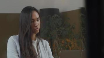 ung kvinna med blandad ras sitter vid bordet, tittar på bärbar dator framför sig, pratar och ler