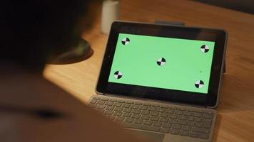close-up da tela verde no laptop, dedos da mulher madura negra tocando o teclado