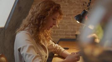 ung vit kvinna sitter vid bordet, skriver på mobiltelefonen framför sig, tittar upp, tänker, fortsätter att skriva video