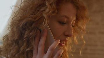 närbild av ung vit kvinna, ringer med mobiltelefon, pratar och ler video