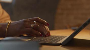 feche os dedos de uma mulher negra madura digitando no laptop video