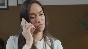 jovem mestiça recebendo uma ligação, segurando o celular na orelha, falando animadamente