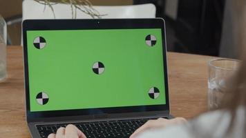 close-up da tela verde no laptop, dedos de uma jovem mulher de raça mista no touch pad do teclado