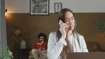 jovem mestiça recebendo uma ligação, falando animadamente, jovem homem do Oriente Médio no sofá no fundo com um livro, ouvindo uma mulher video