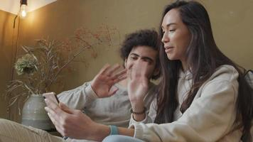 mulher jovem mestiça e homem do Oriente Médio sentado no sofá, mulher segurando o telefone, ambos acenando para se despedir, sorrindo para a tela