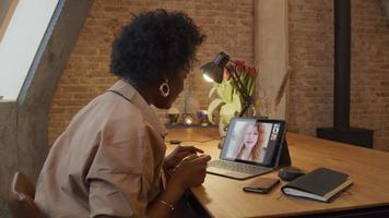 mulher negra madura se senta à mesa, fazendo videochamada, conversando com uma jovem mulher branca video