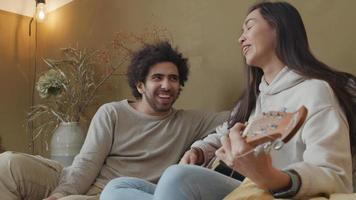 ung kvinna i blandras och ung man från Mellanöstern som sitter på soffan, kvinnan spelar gitarr medan man pratar och skrattar med mannen