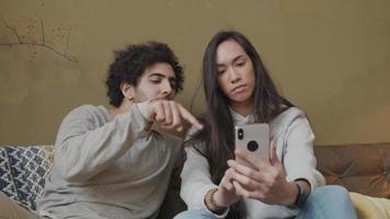 mulher jovem mestiça e homem do Oriente Médio sentado no sofá, mulher segurando o telefone, ambos gesticulando para a tela, sem áudio