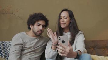 Mulher jovem mestiça e homem do Oriente Médio sentado no sofá, mulher segurando o telefone, ambos acenando, sorrindo para a tela video