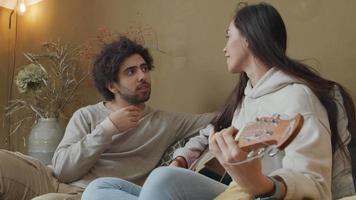 Mulher jovem mestiça e homem do Oriente Médio sentado no sofá, mulher tocando violão enquanto fala com o homem video