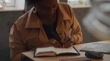 mulher negra madura sentada à mesa, fazendo videochamada, escrevendo no caderno video
