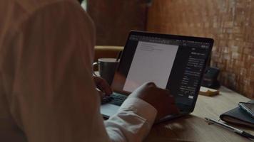 schwarzer Mann, der Brille trägt, am Tisch sitzt und auf Laptop schreibt