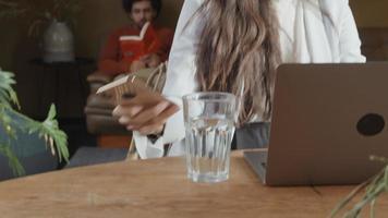 jovem mestiça se senta à mesa com um laptop, atende o telefone, fala, sorri, jovem homem do Oriente Médio lendo no sofá ao fundo