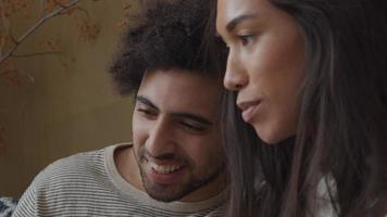 mulher jovem mestiça e homem do Oriente Médio sentado no sofá, mulher segurando o telefone, sorrindo, falando, ambos acenando para o telefone video