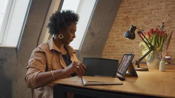 mulher negra madura se senta à mesa, tendo videochamada com jovem branca, mulher negra escreve no caderno