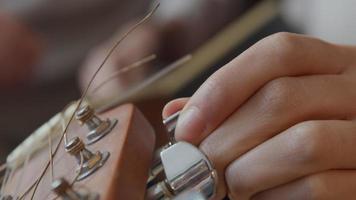 närbild på handen av ung blandad ras kvinna justera tuners på headstock av gitarr