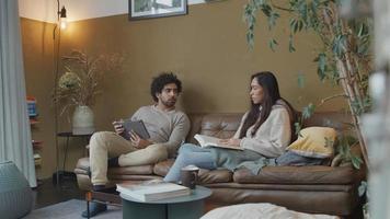 Joven mujer de raza mixta y joven hombre de Oriente Medio sentado en el sofá, la mujer lee el libro, el hombre mira la tableta, ambos hablando