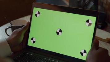 Cerca de la pantalla verde en el portátil, las manos del hombre negro sosteniendo la pantalla video