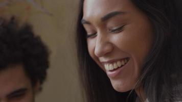 närbild av ung blandad ras kvinna och ung Mellanöstern man sitter på soffan, kvinna spelar gitarr, skrattar och pratar med mannen