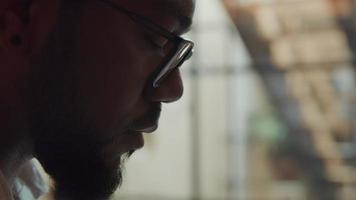 närbild av svart man bär glasögon, prata, tittar på bärbar dator