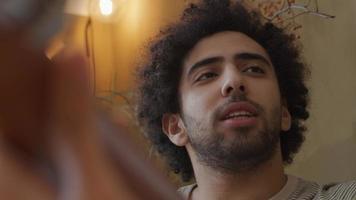 foto de um jovem homem do Oriente Médio conversando com uma jovem mestiça que toca violão video