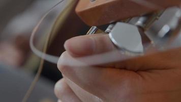 Cerca de los dedos de la joven mujer de raza mixta, girando el afinador de la guitarra, la otra mano toca la cuerda para afinar video