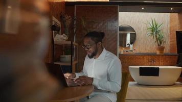 homem negro de óculos, sentado à mesa, digitando no laptop, rindo e falando