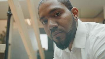 homem negro inclinado no corrimão, olhando para o celular, rosto voltado para a câmera video