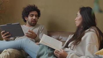 mulher jovem mestiça e homem do Oriente Médio sentado no sofá, mulher lendo livro, homem segurando tablet, falando agitado video
