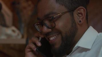 närbild på svart man bär glasögon, mobiltelefon på örat, pratar, ler, avslutar samtal, tittar på skärmen bärbar dator