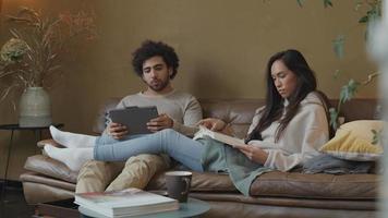 mulher jovem mestiça e homem do Oriente Médio sentado no sofá, mulher lendo livro, homem olhando para tablet