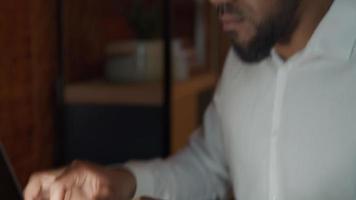 perto de digitar os dedos no laptop de um homem negro de óculos, reflexo da tela no rosto video