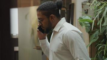svart man bär glasögon, väljer nummer på mobiltelefon, telefon på örat, börjar prata och går i vardagsrummet