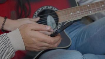 Hand with mobile phone of young Middle Eastern man holding in front of guitar of young mixed race woman, turning tuner of guitar