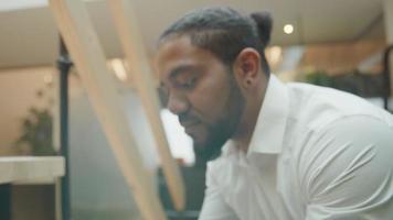 homem negro inclinado no corrimão, olhando para o celular, rosto virado para a câmera, sorrindo video