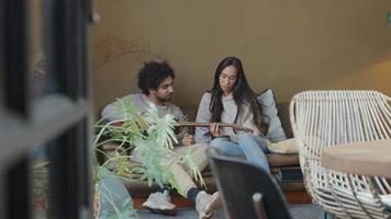 Joven mujer de raza mixta y joven del Medio Oriente sentado en el sofá, el hombre sostiene la guitarra, la mujer le muestra cómo jugar