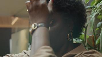 närbild av svart mogen kvinna som ser till mobiltelefon hålls i luften, justera håret video