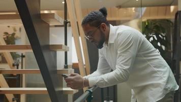 homem negro de óculos, segurando o celular na frente dele, tocando a tela, apoiando-se no corrimão no corredor video