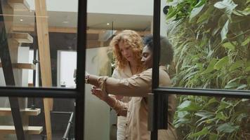mulher negra madura e jovem branca em pé no corredor, mulher negra tira foto deles com o telefone celular, sorrindo