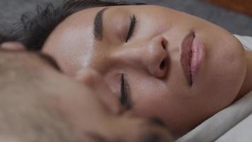 close-up de uma jovem mulher mestiça, conversando, sorrindo, deitada de costas no chão com um jovem homem do Oriente Médio