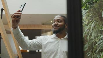 homem negro em pé, segurando o celular no ar, seguindo a si mesmo fazendo vídeo, sorrindo video