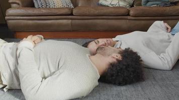 ung kvinna med blandad ras och ung man från Mellanöstern som ligger på ryggen på golvet, i motsatt riktning, huvud som rör vid axeln, pratar