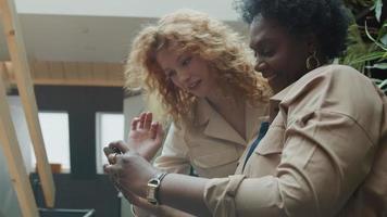 mulher negra madura e jovem branca em pé no corredor, olhando e apontando para o telefone celular, sorrindo