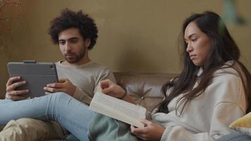 jonge gemengd ras vrouw en jonge Midden-Oosten man zittend op de bank, vrouw leest boek, man houdt tablet, serieus praten video