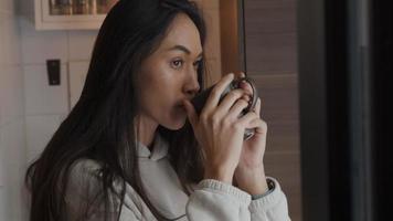 jonge vrouw van gemengd ras die een slokje uit de beker neemt, terwijl ze contemplatief door het raam kijkt
